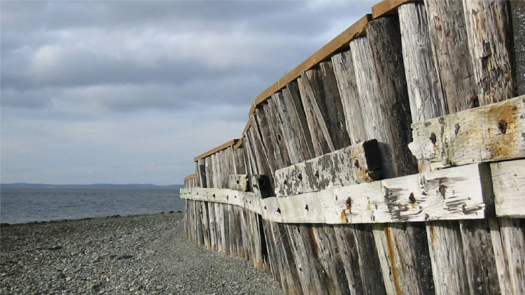 Old wooden bulkhead on a beach with a view of the water